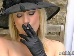 Sexy blonde smoking seductively and flashing pussy in leather gloves and silky nylons