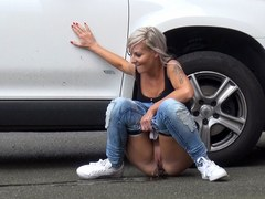 Blonde Pissing Next To A Parked Car